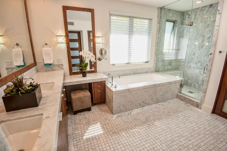 This contemporary bathroom's shower, bathtub and countertops display a gorgeous white marble that gives the space an open, airy feel. The glass door to the shower enhances the spacious feeling and connects the shower space to the rest of the room.
