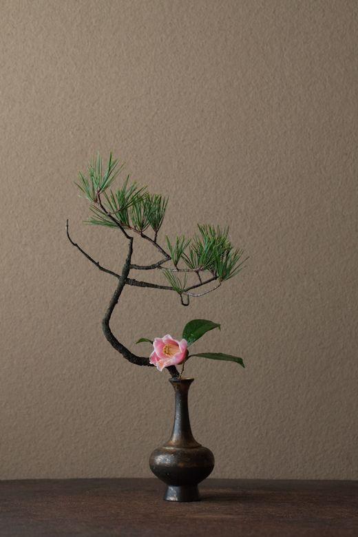 2012年1月6日(金)    天下太平を願い、「日の出」のような花に。  花=松(マツ)、椿(ツバキ)  器=金銅華瓶(鎌倉時代)