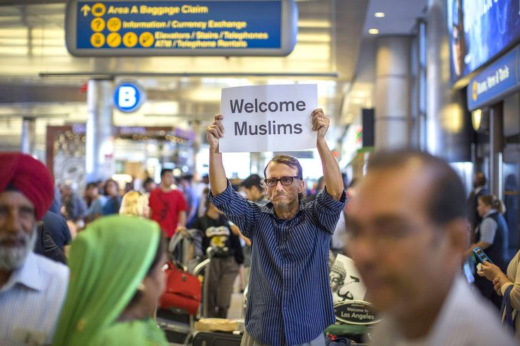 "Jun 2017 - John Wider w/ a ""welcome"" sign near arriving Sikh trav. at L.A. Intern'l Airport, the 1st day of the partial reinst't of Pres. Trump's travel ban, which has temp. barred trav. from 6 Muslim-majority countries from entering the US. Under a Supreme Court order, trav. who don't have a ""bona fide relationship"" w/ a someone in the US, can be turned away. The ban affects travelers from Iran, Libya, Somalia, Sudan, Syria & Yemen 