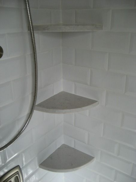 Fantastic shower with beveled subway tile surround and Silestone Lagoon Shelves.