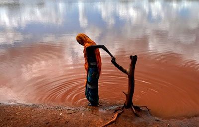 Una donna va a prendere l'acqua in una pozza inquinata nel villaggio di Dambas,  a 80 km da Wajir, nel nord del Kenya
