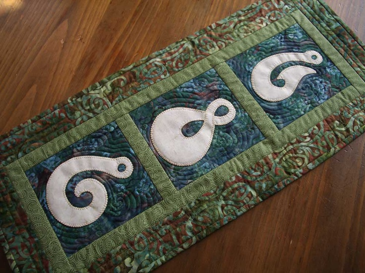 Bone carving wallhanging.  Designed by Mary Metcalf.  The Maori have long carved their fish hooks and pendants from pounamu (greenstone) or bone.   This wall hanging shows three distinct types of carving and each has a meaning.