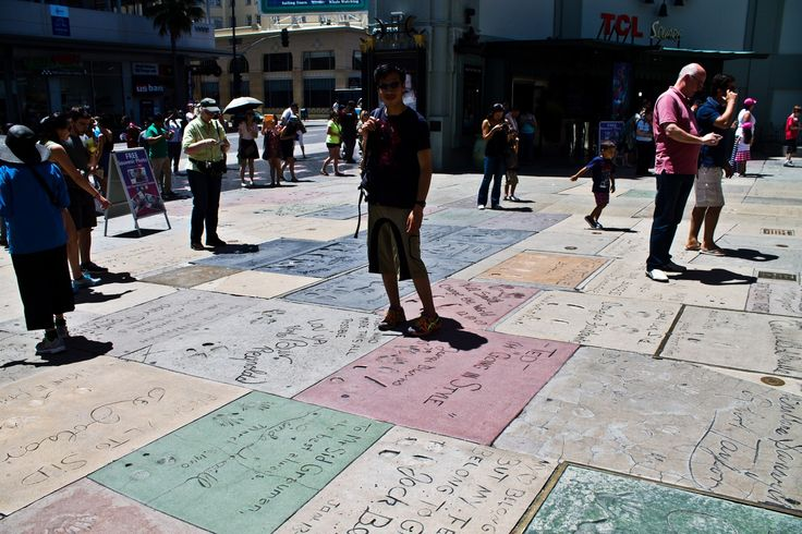At the Chinese Theatre Forecourt looking at the handprints and footprints of the stars past and present