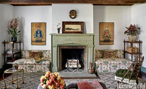 """In aNew York home, the living room's banquettesflank a mantel with a combed faux finish by Dean Barger. """"We don't do animal prints often,"""" designerAnne Maxwell Foster says of the pillows. """"But Scalamandré's Tigre velvet is so luxe and warm, it worked here."""" The 1876 chair is by George Jacob Hunzinger. A Bunny Williams for Dash & Albert rug was cut and trimmed to fit around the hearth."""