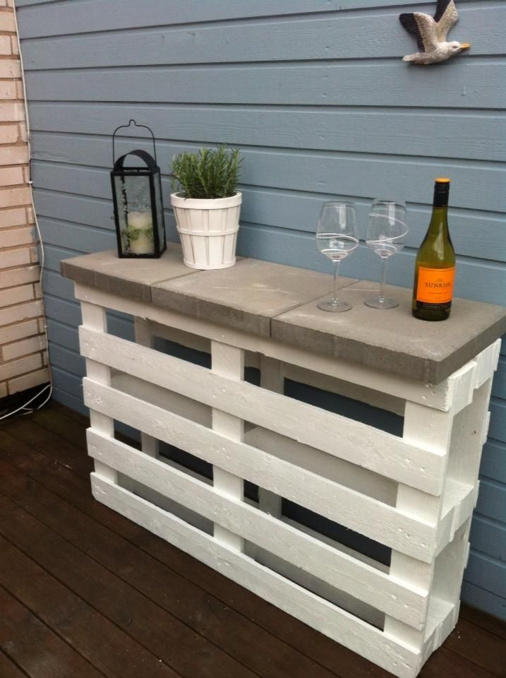 Two pallets back-to-back, painted a lovely color, and topped with paving tiles, makes a lovely DIY shelf for the patio.