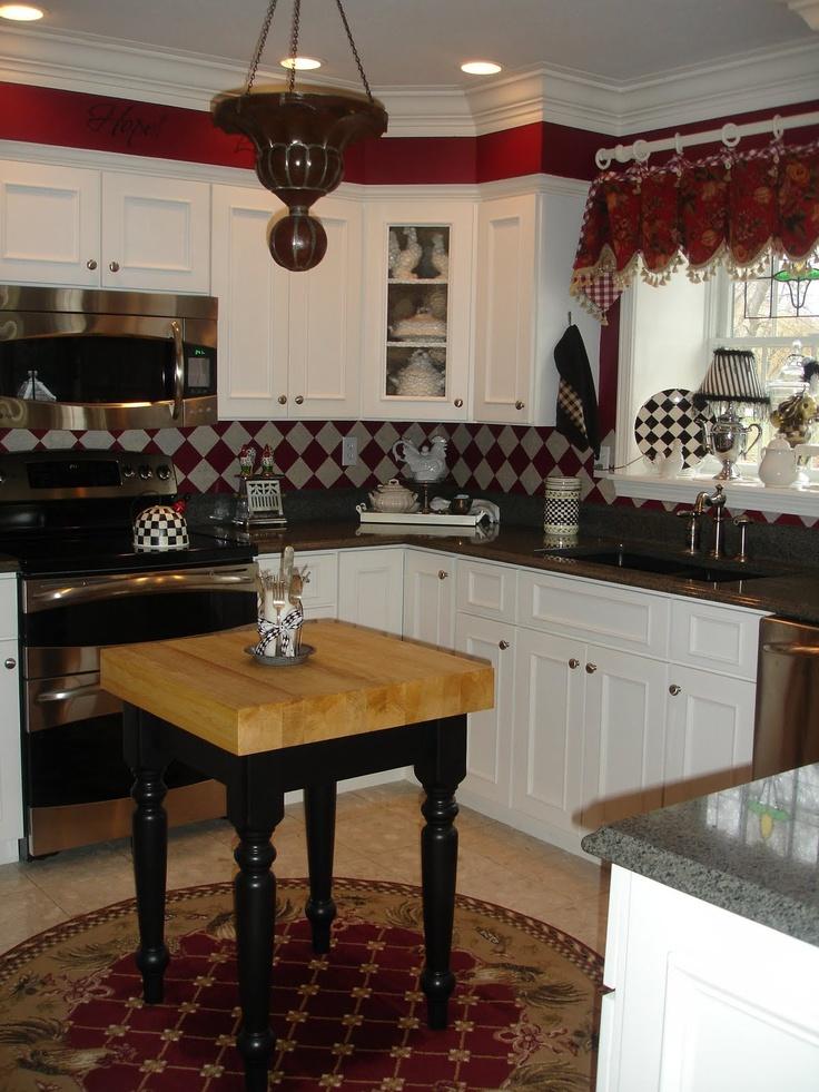 white cabinets, beige/neutral floor, dark counters, red ...
