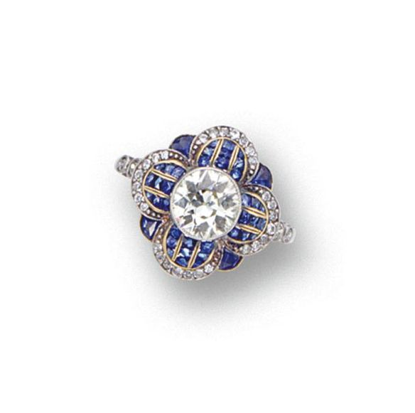 DIAMOND AND SAPPHIRE RING.  Set with an old European-cut diamond weighing approximately 1.00 carat, within a modified floral motif set with French calibré-cut sapphires and small old European-cut diamonds, mounted in platinum. Art Deco or Art Deco style. [I want to say Art Deco revival, but in any case, that's the closest I can guess without a definitive date]