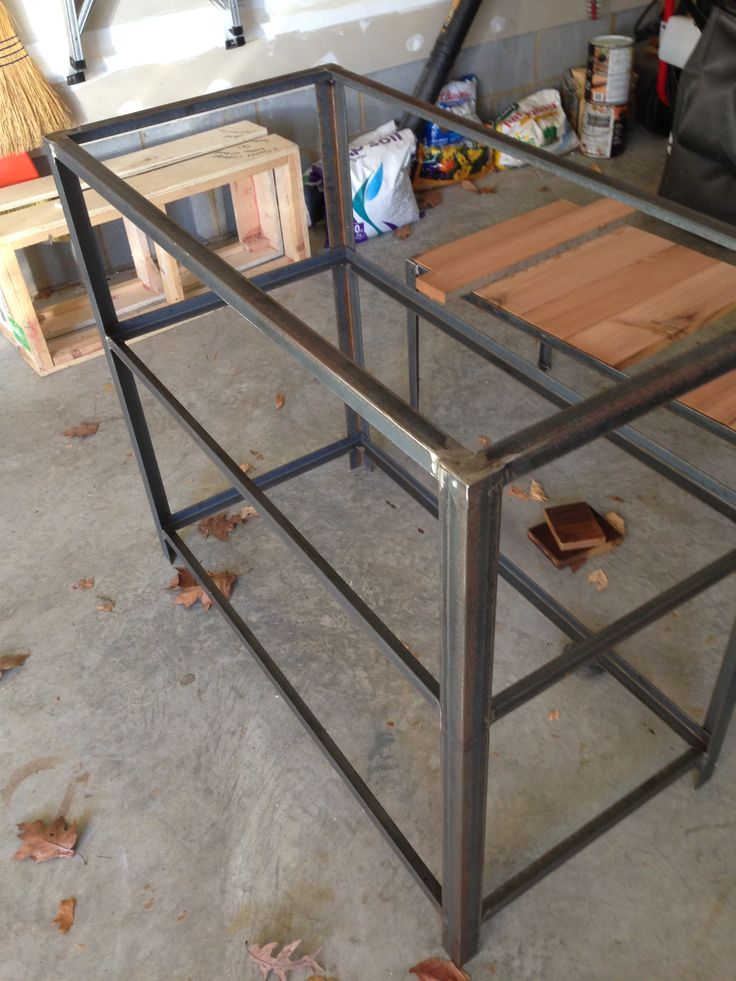 Iron base for industrial bar cart.  Bottom shelves have drop in wood shelf, top shelf overhangs like a table top