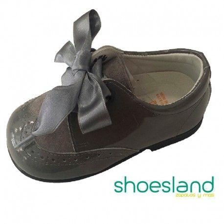 Zapatos tipo blucher para niña de Andanines para dar sus primeros pasos en un elegante charol color gris ceniza con dulce detalle de serraje picado en el frontal atados con cordones al tono o lazo de raso.  Desde el 18 hasta el 24