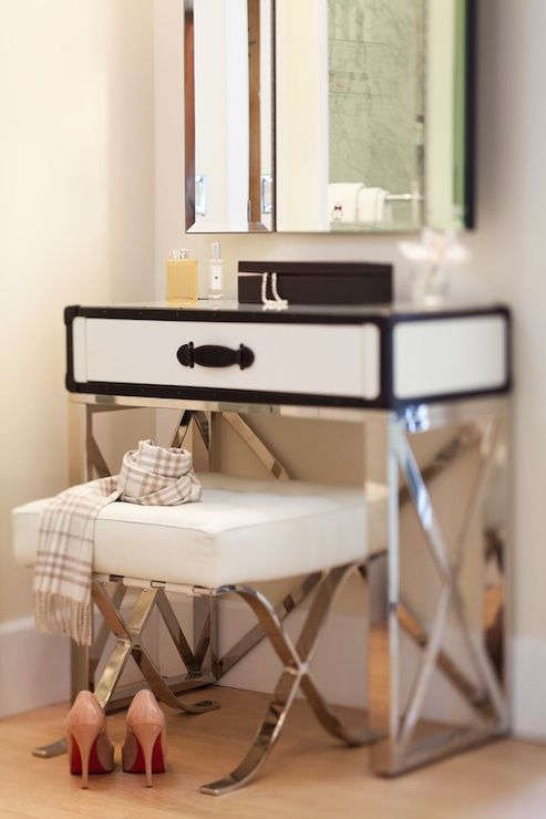 Chic dressing area features beveled mirror over contemporary steamer trunk dressing table on x base paired with a Barcelona white leather vanity stool.