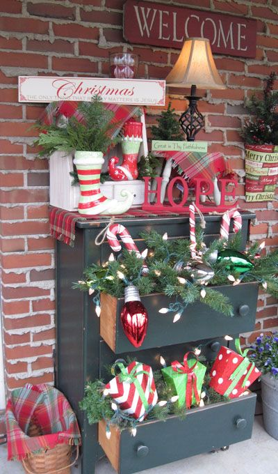 Christmas porch decor: a dresser overflowing with greens, lights & gifts
