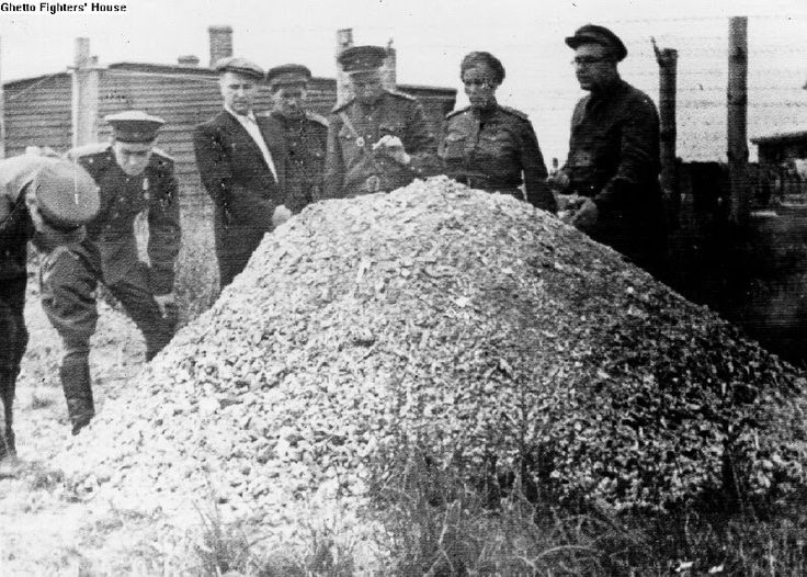 Soviet soldiers standing beside a pile of human bone fragments from a crematorium, after the liberation of Majdanek concentration camp, 1944