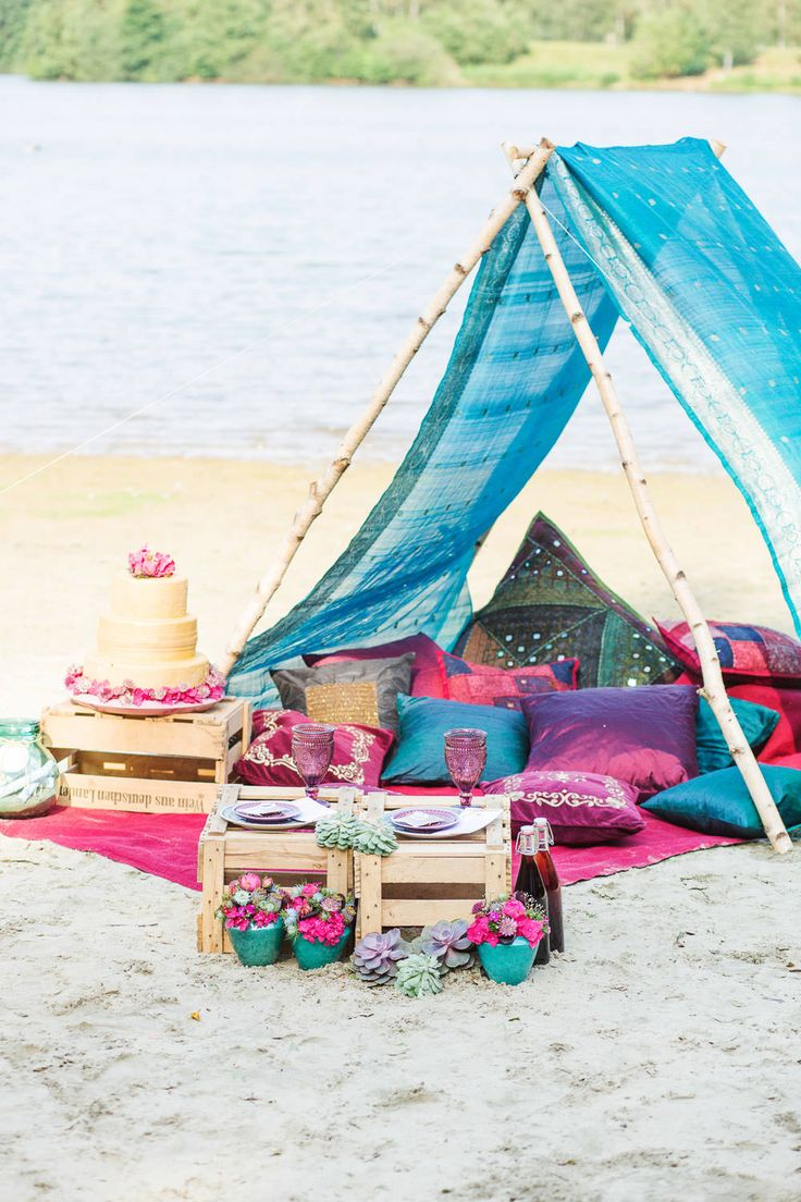 A tipi, tent made up of a brightly coloured sari & sumptuous velvet & satin cushions with wooden crates as tables