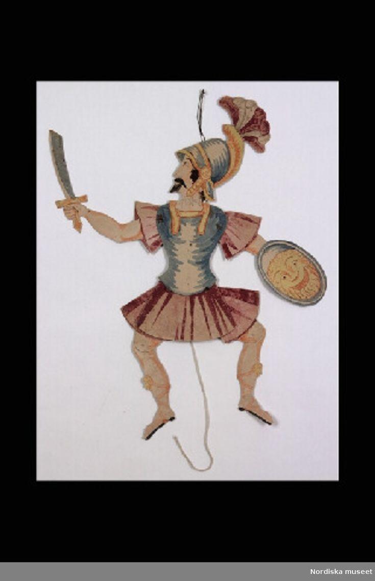 Inventering Sesam 1996-1999: H 38 cm Sprattelgubbe av handkolorerad kartong föreställande man med mörkt hår, mustasch och skägg, klädd i rustning,  lila kjol, bröstplåt, hjälm med fjädrar, svärd och sköld. Om man drar i snöret rör sig armarna och benen.  Helena Carlsson 1996