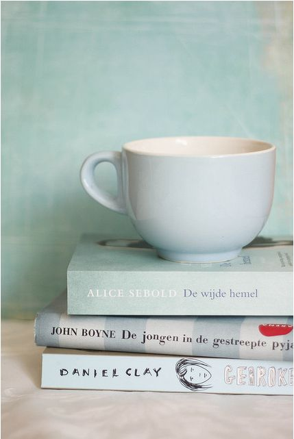 Like the idea of the mug on top of a stack of books. We'd do different color scheme- maybe two black books with gold writing and one colorful book, with a black background.