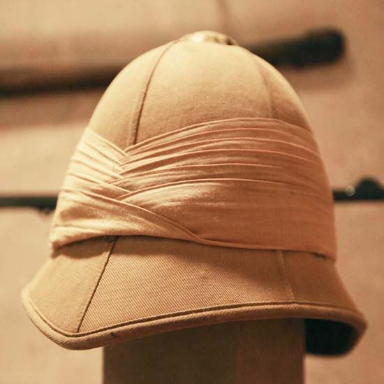 victorian Pith helmet.. The pith helmet (also known as the safari helmet, sun helmet, topee, sola topee, salacot or topi is a lightweight cloth-covered helmet made of cork or pith, typically pith from the sola, Aeschynomene aspera, an Indian swamp plant, or A. paludosa, or a similar plant. Designed to shade the wearer's head and face from the sun, pith helmets were often worn by people of European origin in the tropics, but have also been used in other contexts.