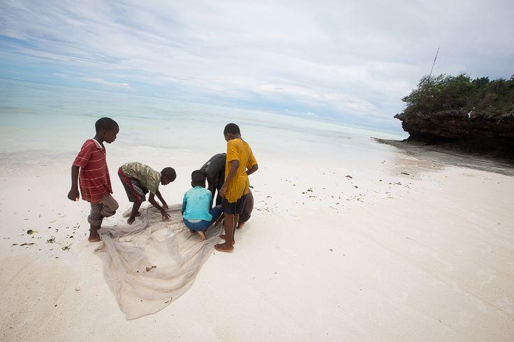 Children fishing in Mfumbwi beach in Jambiani, Zanzibar