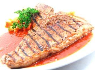 Grilled Australian T.BONE STEAK, served with pomme gratin, regular vegetables and BBQ sauce.