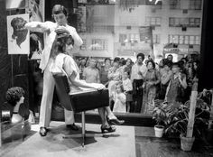 Vidal Sassoon cuts hair in the window of his salon in New York in the 60's.