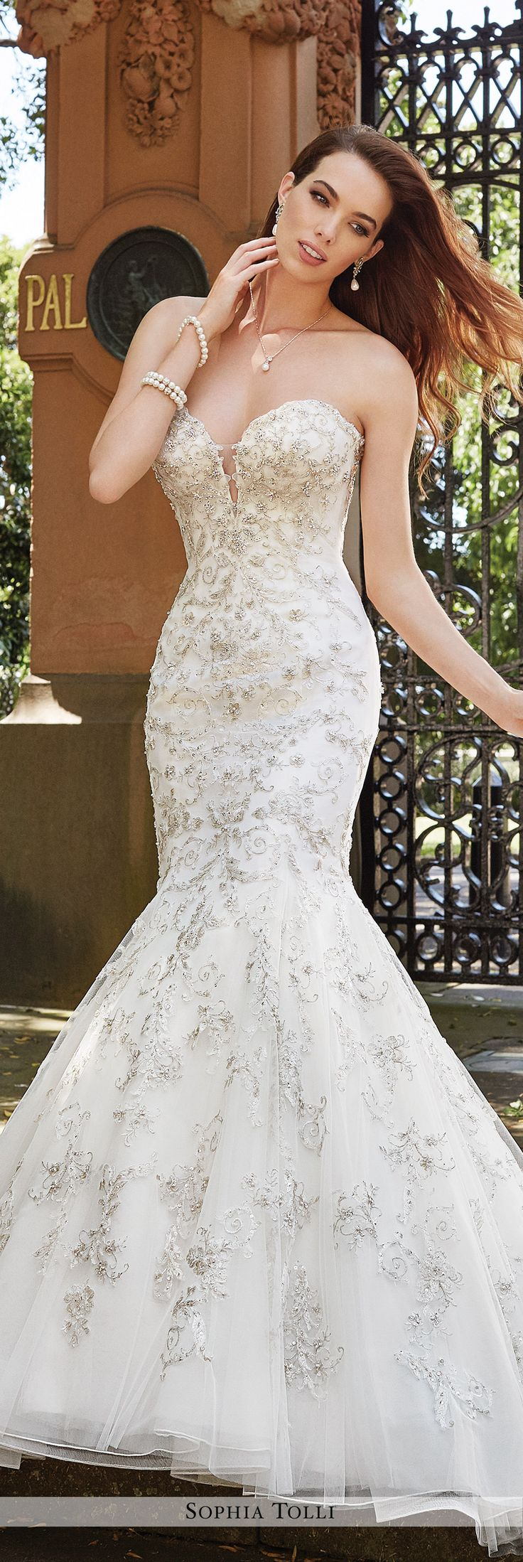 Sophia Tolli - Y21659 Palermo - Strapless soft tulle trumpet gown with crystal hand-beaded lace appliqués, deep sweetheart neckline with sheer panel, dropped waistline, back corset, voluminous back skirt with chapel train. Removable spaghetti and halter straps included.Also available with a back zipper trimmed with diamante buttons and loops as Y21659ZB.Sizes: 0 - 28Colors: Ivory/Pewter, Ivory, White