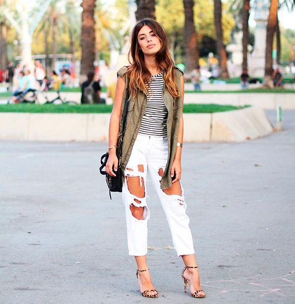 Street style da blogueira Aida Domenech com blusa listrada, calça branca destroyed e colete militar.