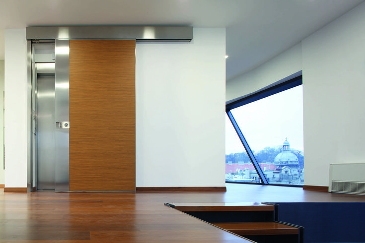 The sliding safety door Vela with vertical slats allows designing a door reaching up to the ceiling and turning it into a moving architectural feature.