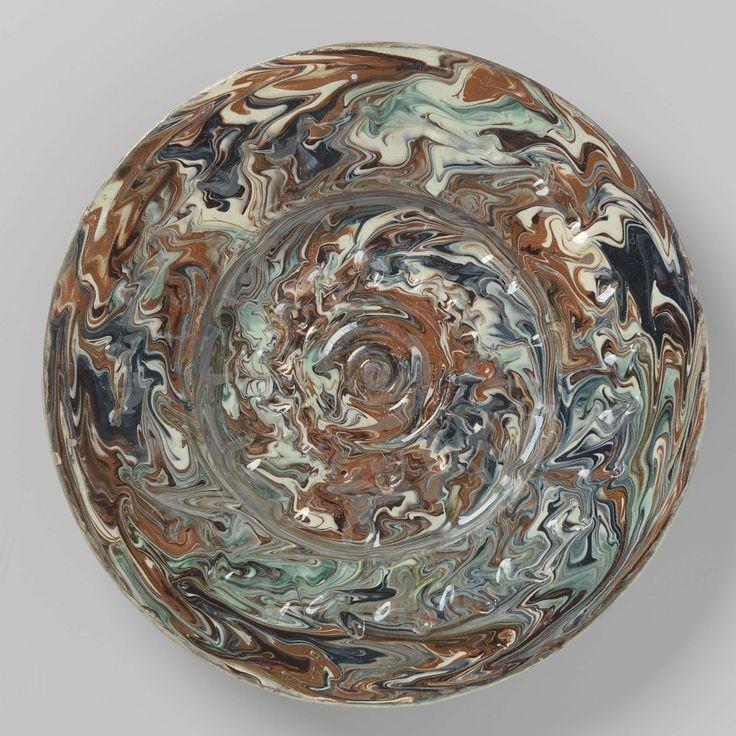 Anonymous   Schotel van loodglazuur aardewerk, met verdiept plat. Versierd met cirkels in reliëf en noppen afgewisseld met kuilen. Veelkleurige sliblagen., Anonymous, c. 1575 - c. 1625   Schotel van loodglazuur aardewerk. Het plat is verdiept en versierd met drie concentrische cirkels in relief, waar omheen twee cirkelvormig gerangschikte reeksen van kuiltjes. De brede rand heeft een reeks noppen afgewisseld met kuiltjes. De schotel is bedekt met roodbruine, blauwe, groene en paarse en…