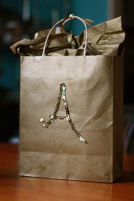 Glue a sequin strand initial onto a brown paper gift bag to spice things up!