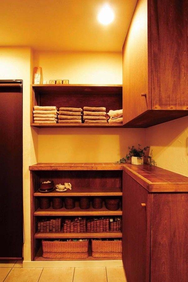 収納小物は色を限定するとすっきりと片付いて見えます。 洗面室の収納カウンター。タオル類はブラウンなどのナチュラルカラーで統一し、細々とした小物はブラウン系のカゴで隠す収納にしています。アンティークな雰囲気の収納家具と調和してすっきりと見えます。