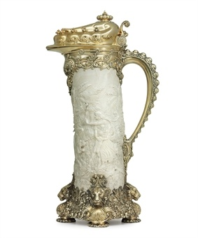"A MONUMENTAL SILVER-GILT & CARVED IVORY TANKARD,   MARK OF TIFFANY & CO., NEW YORK, CIRCA 1901  The ivory tusk body, on lozenge-form silver-gilt base cast & chased with underbrush, set on four knobbed feet and with spiraling plant-form joins above tiger's heads at intervals, the silver-gilt handle with spiraled beading & scrolling rosette-studded joins. This tankard is described in the Tiffany pattern book as ""Tiffany Ivory Tusk E. Ind."" with a silver weight of ""209.9 ozt.""  26 in. high"