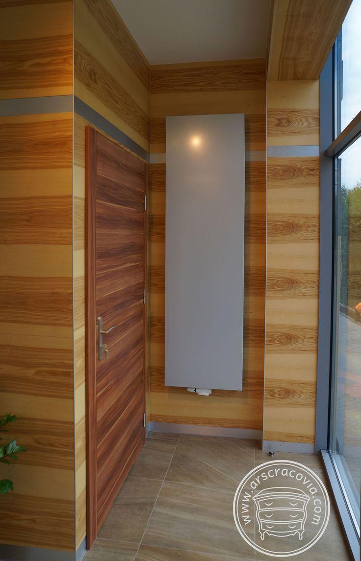 Okładziny ścian kawiarni z drzwiami, wykonane z naturalnego jesionu. Naroża zabezpieczone przed ubiciem systemowymi profilami alu.