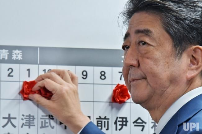 Shinzo Abe, President of Liberal Democratic Party of Japan, places a red rosette on the name of elected LDP candidates during the ballot…