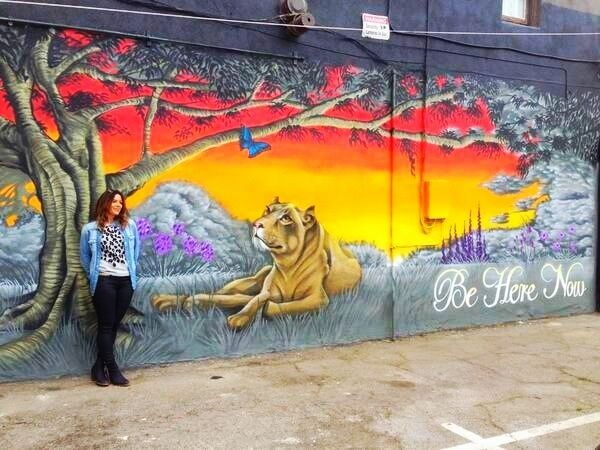 @maybemcqueen Vashti Whitfield in front of beautiful #BeHereNow mural