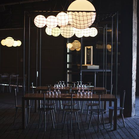'The Blocks' - a temporary wine bar in Sydney, by Studio Toogood! - Groups of spherical lamps representing grapes are bunched overhead behind wire netting.