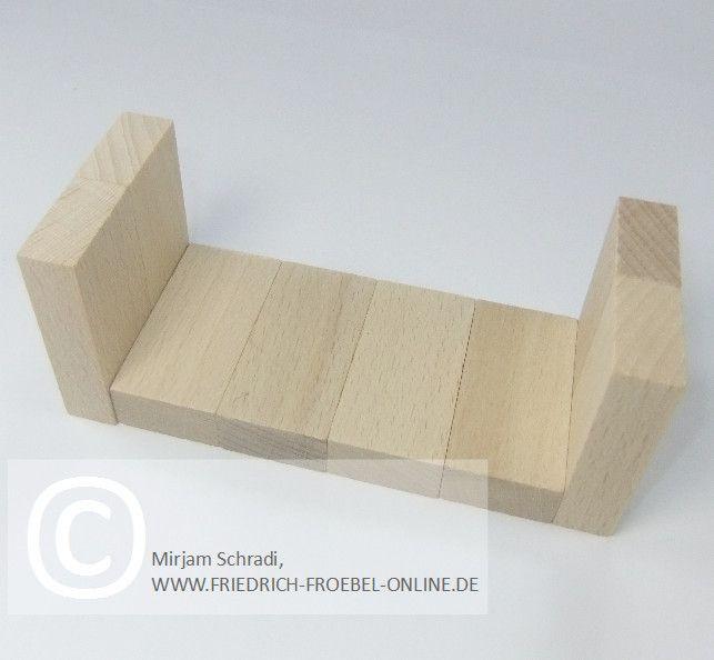Bett aus Holzbausteinen natur mit Spielgaben nach Froebel (Spielgabe 4)