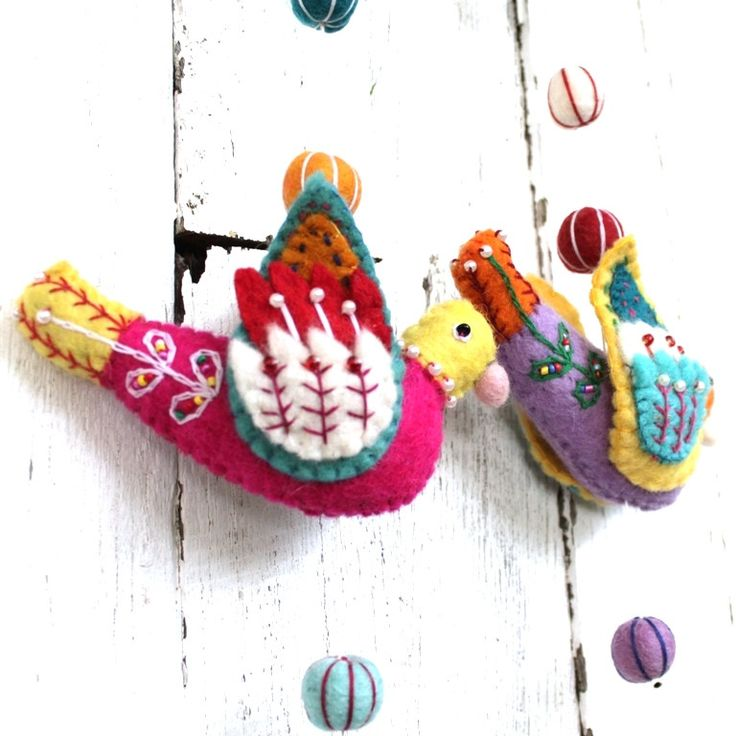 Wonderfully creative single strand felt bird mobile. They look lovely in a child's room and are embellished with decorative stitching and small 'pearl' beading. Wildly colourful, they add instant pop to any space and are a true delight to look at.Each individual strand is different in it's own unique way, but they are all stunning and this only adds to their charm, (ie you will not receive the piece/s in the images).Featuring a small brass bell on the bottom.FIBRE: Hand felted WOOL with…