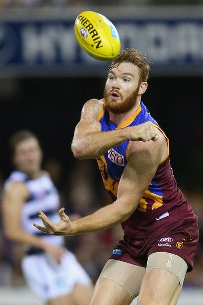 Daniel Merrett of the Lions handballs during the round 13 AFL match between the Brisbane Lions and the Geelong Cats at The Gabba on June 23, 2013 in Brisbane, Australia.