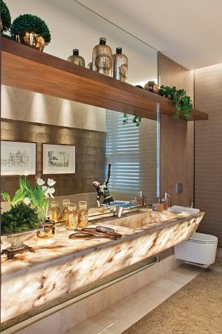O lavabo, com bancada em ônix iluminado e monocomando Hansgrohe (Vallori).