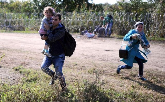 ヨーロッパ移民問題の現状 > セルビアとハンガリーの国境線を走る移民の家族。2015年8月28日、ハンガリー・ロスケ。