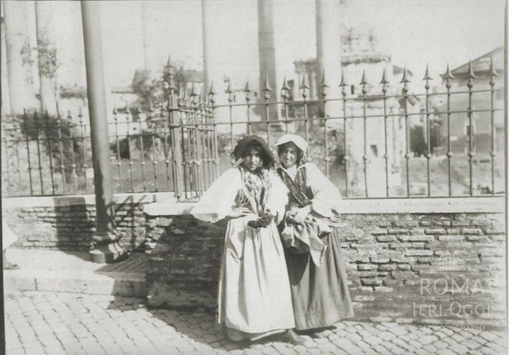 Via della Consolazione (1900 ca) Alle spalle delle due ragazze in costume si riconosce la Chiesa dei Santi Luca e Martina e la Curia Iulia.