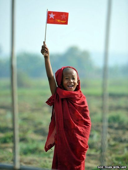A Buddhist novice waves a National League for Democracy flag as Burma's opposition leader Aung San Suu Kyi arrives at an electoral campaign rally in Naypyidaw.