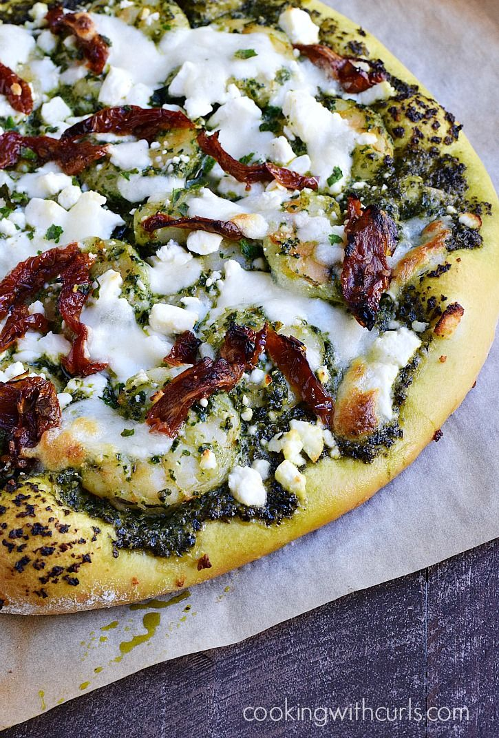 Shrimp Pesto Pizza topped with kale pesto, sun-dried tomatoes, feta and mozzarella cheese on a homemade crust.