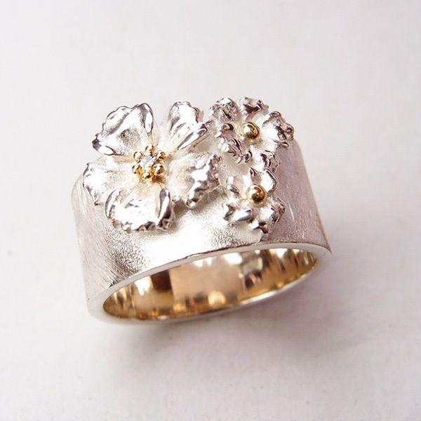 Emenel.  Zilveren ring met twee kleine en één grote Anemoon gezet op een brede ring. De grote Anemoon heeft een gouden 6 poot zetting die een briljant vasthoudt van 0.015ct.