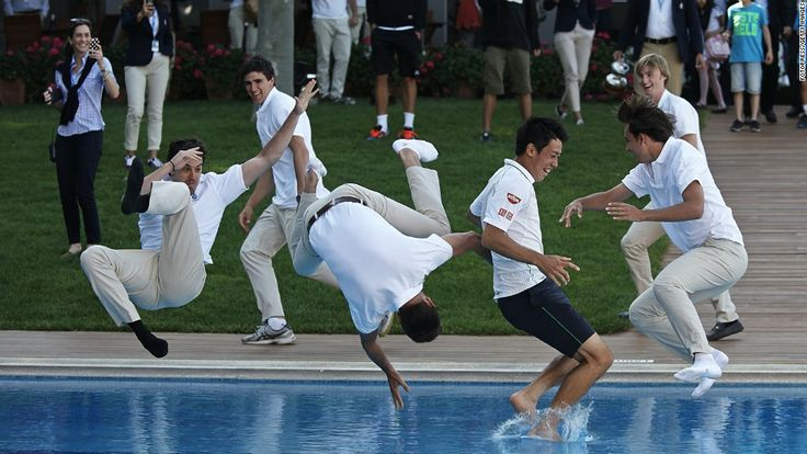 Pro tennis player Kei Nishikori, second from right, is thrown into a pool after winning the final of the Barcelona Open on Sunday, April 27