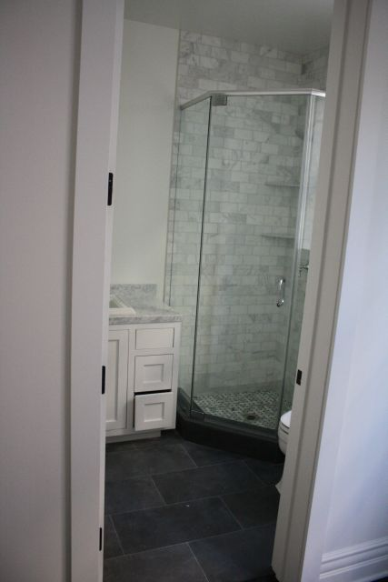 Basalt Floor tile install with white carrera marble bathroom