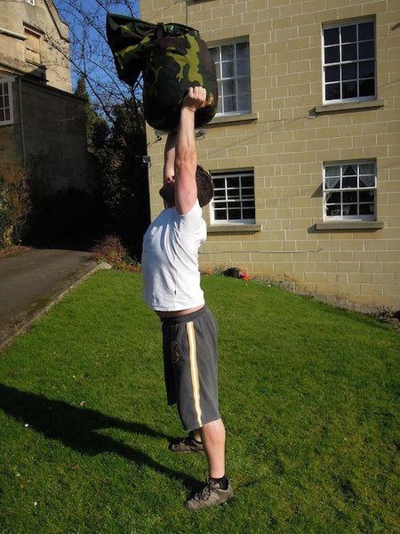 5 Heavy Sandbag Bear Hug Squats, Max Sandbag Overhead Press. Rest for 2 - 4 minutes and repeat for a total of 5 rounds.