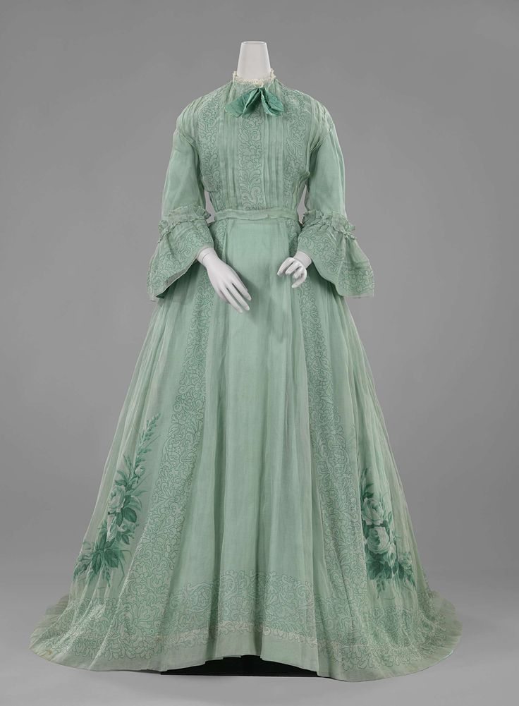 1863-66 Dress with three-quarter sleeves with ruffles and high neck lace edge of translucent pale green woven cotton, printed with green flowers and leaves (?); green silk bow, anonymous.
