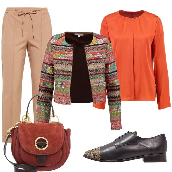 Pantalone comodo, camicia arancio senza colletto che si intravede sotto la giacca in lana colorata, grazie al suo taglio particolare. La scarpa bassa stringata con punta color oro e borsa piccola a tracolla, o a mano, in pelle terra di Siena .