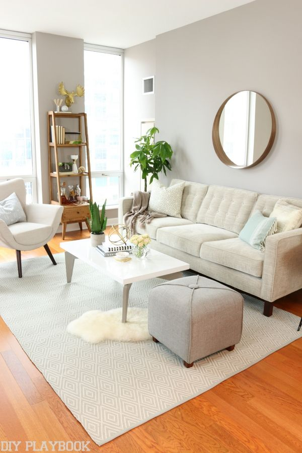 a neutral living room perfect for any city girl love the gold accents and quality apartment furniture layout