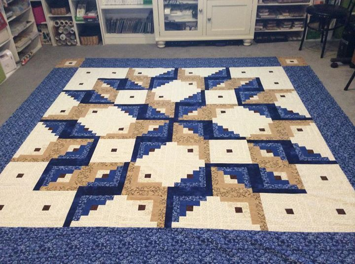 a log cabin quilting pattern completed in a tumbling block pattern called the log cabin carpenter square - king size